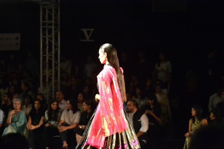 A model walks the ramp in Benarsi black suit
